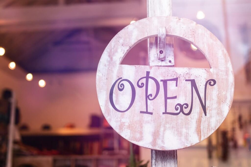 A sign which says open on a local shop window